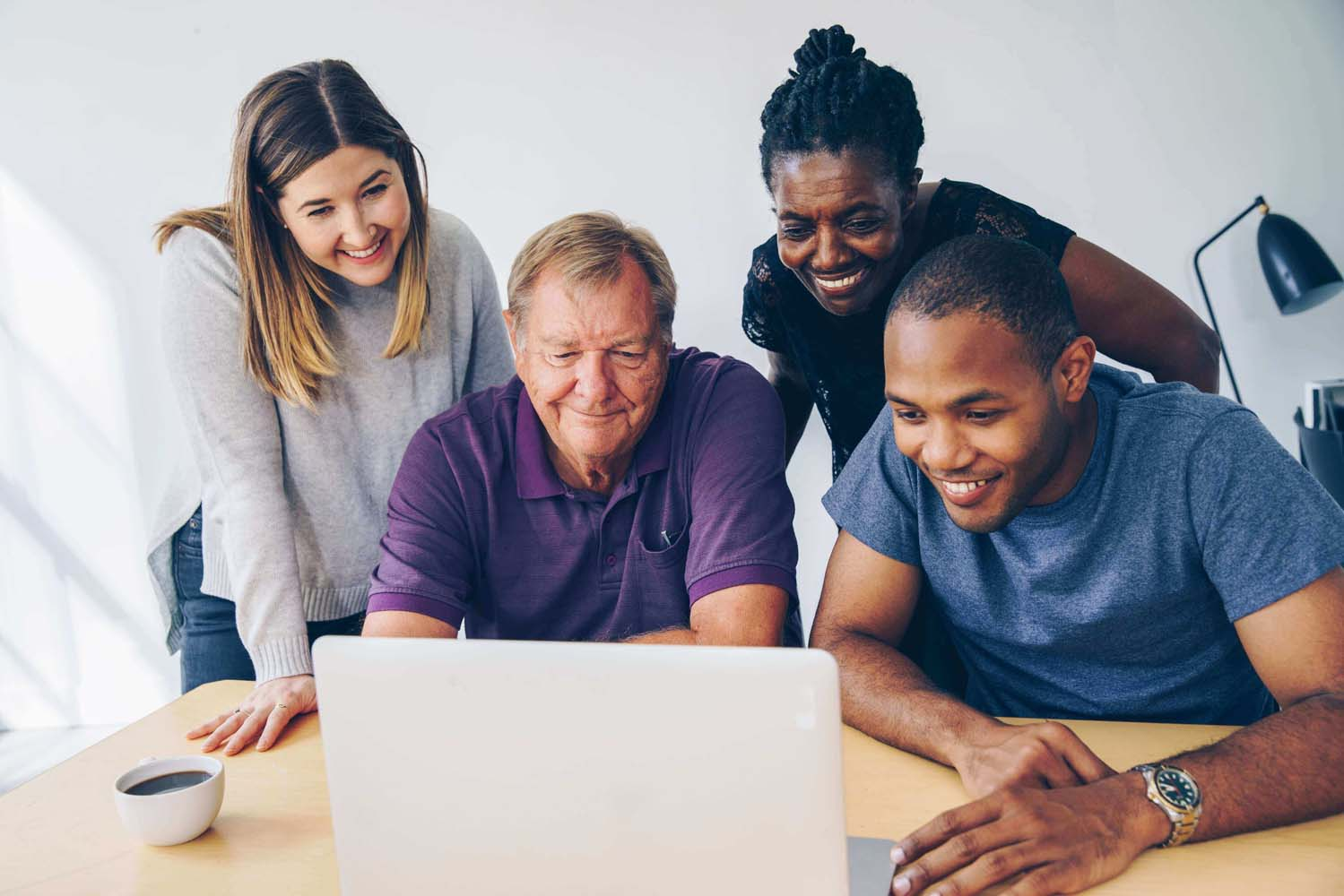 Diverse group of people interacting with laptop